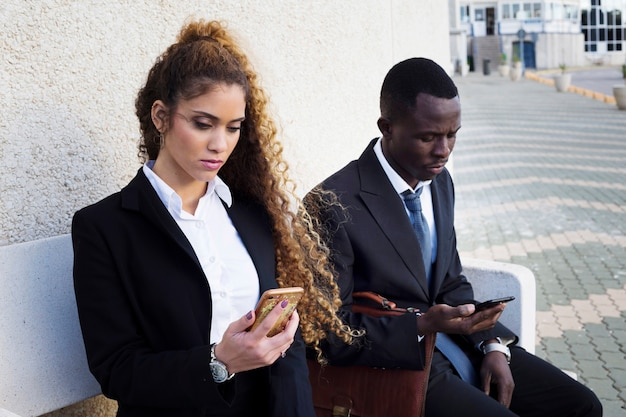 Pareja de gente de negocios mirando a smartphone en banco