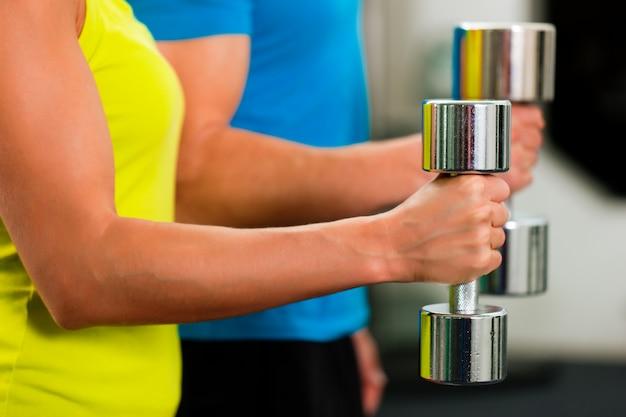 Pareja en el gimnasio haciendo ejercicios con pesas