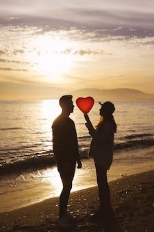 Pareja con globo de corazón en la orilla del mar en la noche
