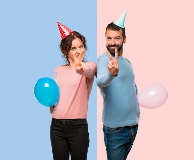 Pareja con globos y sombreros de cumpleaños sonriendo y mostrando el signo de la victoria