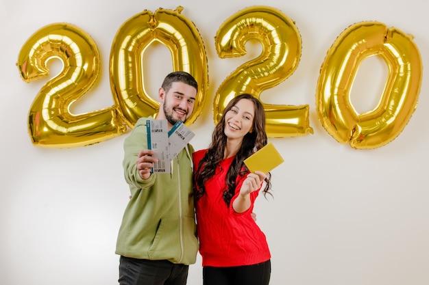 Pareja guapa hombre y mujer con pasajes de avión de plantilla y pasaporte frente a globos 2020
