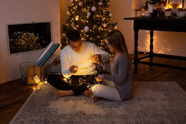 Pareja con guirnalda de navidad en manos