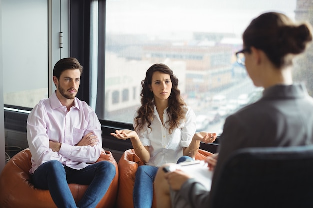 Pareja hablando con un consejero matrimonial durante la terapia