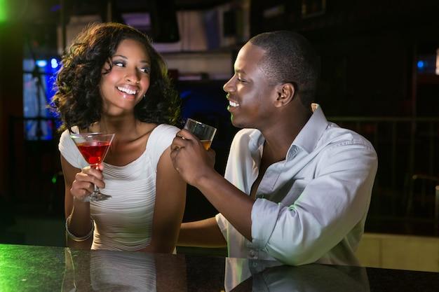 Pareja hablando y sonriendo mientras toma una copa en el mostrador del bar