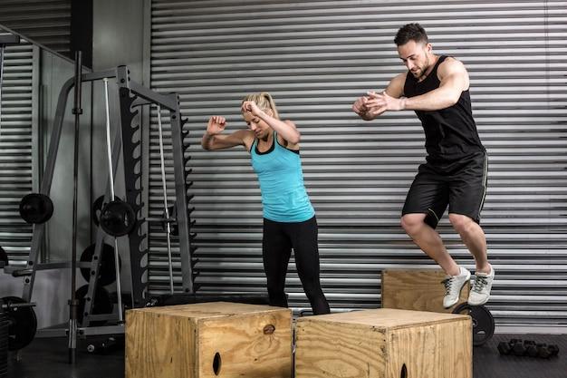 Pareja haciendo caja de saltos en el gimnasio en el gimnasio crossfit