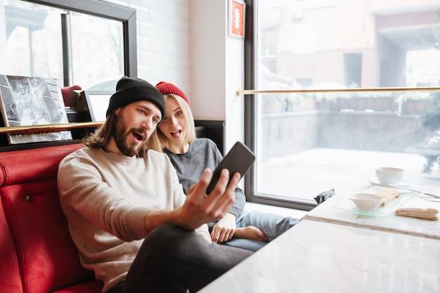 Pareja haciendo selfie en cafe