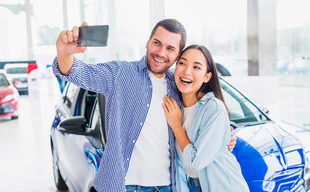 Pareja haciendo selfie en concesionario de coches