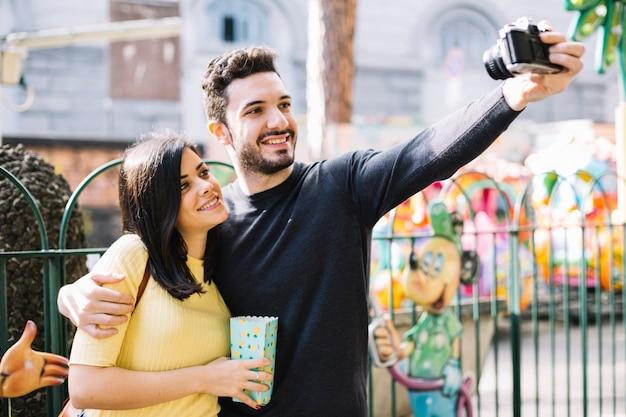 Pareja haciéndose un selfie en el parque de atracciones