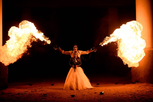 Pareja de halloween de pie con lanzallamas en las manos. gran fuego