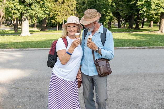 Pareja con helado en la mano caminando por el parque