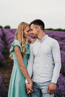 Una pareja hermosa y feliz en el campo de lavanda