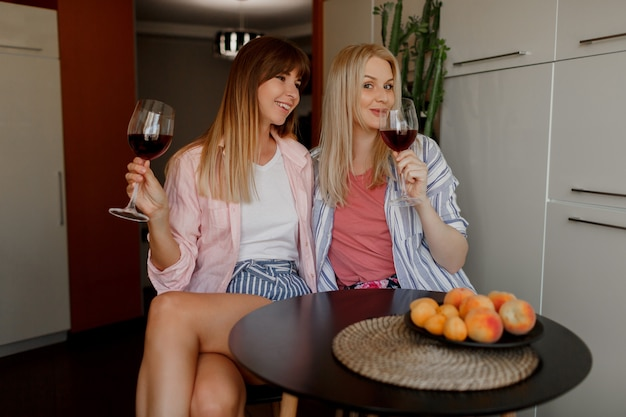 Pareja de hermosas mujeres bebiendo vino en casa. usando pijama.