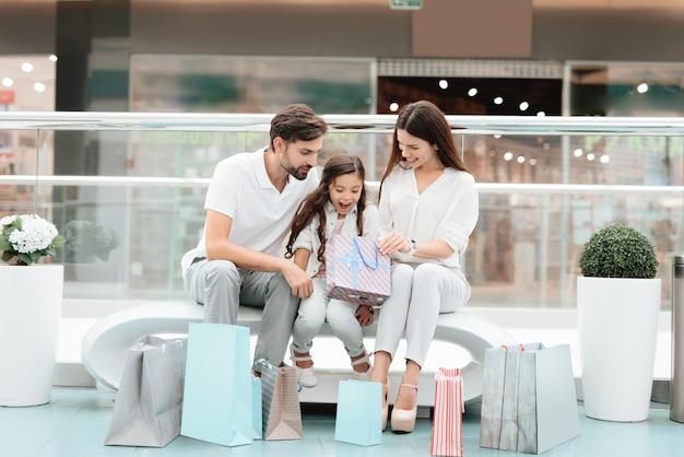 Pareja con hija con bolsas de compras están sentados en el banco