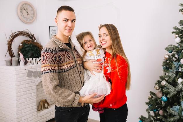 Pareja con hija joven celebrando navidad en casa