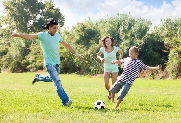 Pareja con hijo jugando con balón de fútbol