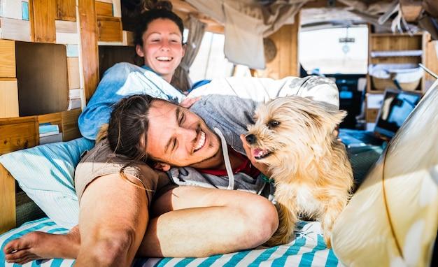 Pareja hippie con perro gracioso viajando juntos en transporte minivan vintage