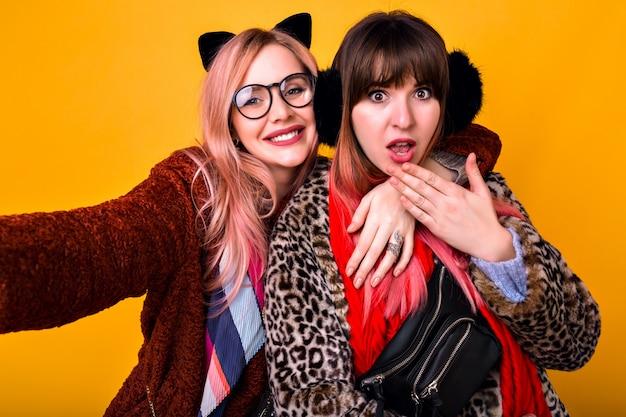 Pareja de hipster bastante divertidas mejores amigas hermanas chicas haciendo selfie en la pared amarilla, mostrando la lengua y sonriendo, vistiendo abrigos de piel estampados de primavera, bufandas, riñonera y gafas transparentes.