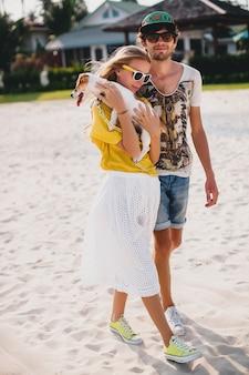 Pareja de hipster con estilo joven inconformista en el amor caminando y jugando con el perro en la playa tropical
