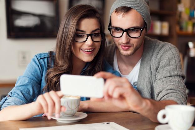 Pareja hipster mediante teléfono móvil en el café