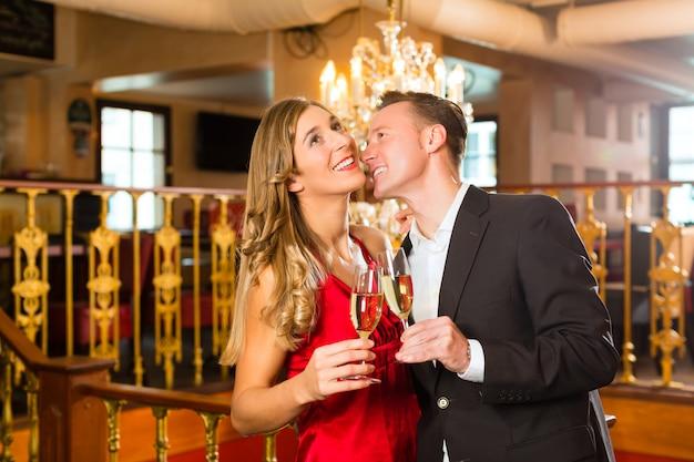 Pareja, hombre y mujer, bebiendo champán en un elegante restaurante, cada uno con una copa de vino espumoso en la mano, una gran lámpara de araña está en
