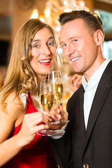 Pareja, hombre y mujer, bebiendo champán en un elegante restaurante, cada uno con una copa de vino espumoso en la mano