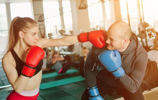 Pareja hombre y mujer de boxeo en guantes de boxeo y ropa deportiva en el gimnasio.