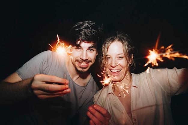 Pareja hombre y mujer caucásica jugando con bengalas