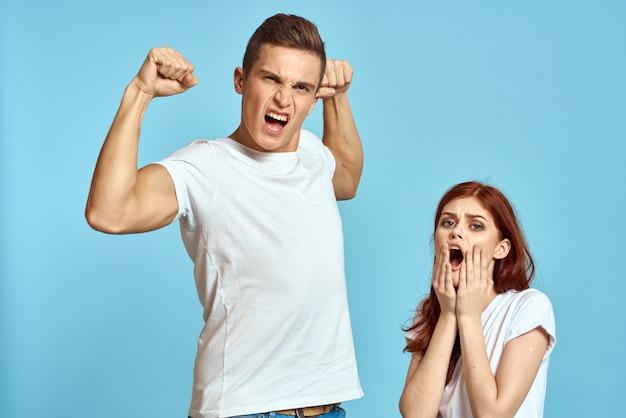 Pareja de hombre y mujer joven en camisetas blancas en un espacio azul claro
