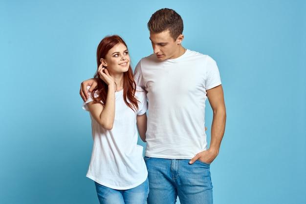 Pareja de hombre y mujer joven en camisetas blancas sobre una pared azul claro