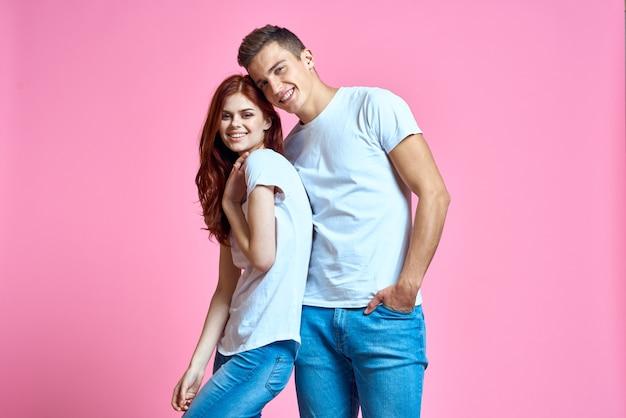 Pareja hombre y mujer posando en camisetas blancas.