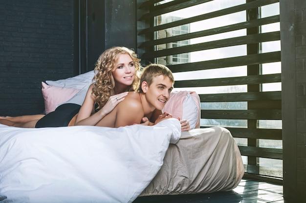 Pareja de hombre y mujer en ropa interior en el dormitorio de una hermosa joven feliz