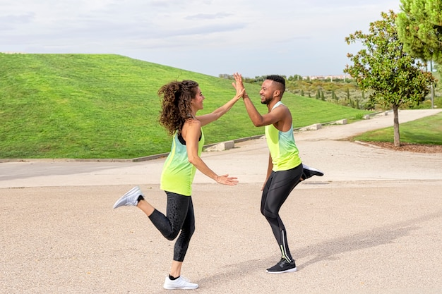 Pareja de hombre negro y mujer blanca son felices haciendo deporte y corriendo, se saludan con las manos, están en el parque vestidos con ropa deportiva