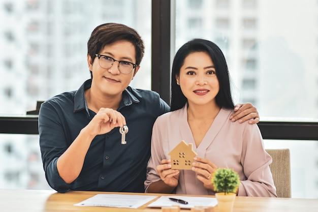 Pareja hombre sosteniendo key y mujeres sosteniendo el modelo de casa para comprar el concepto de casa