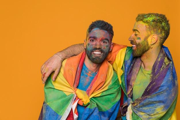 Pareja de hombres homosexuales cubiertos por la bandera lgbt y pintados de colores.