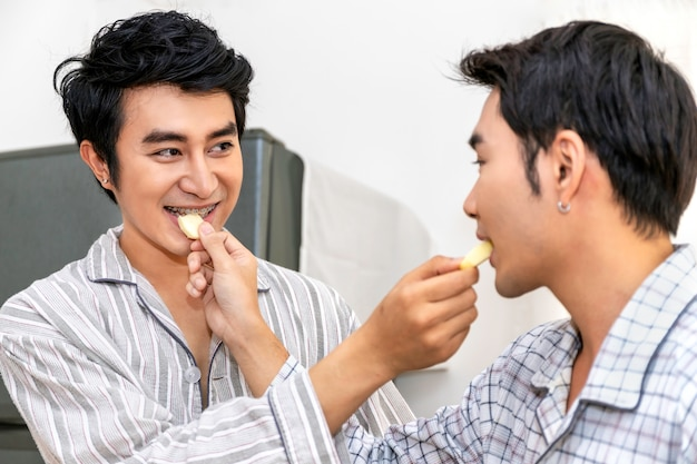 Pareja homosexual asiática come manzana en la cocina