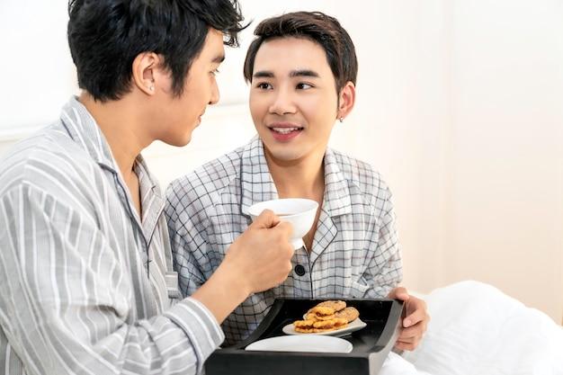 Pareja homosexual asiática en pijama desayunando en la cama