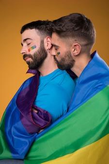 Pareja de homosexuales abrazando amorosamente envuelta en una bandera de arco iris