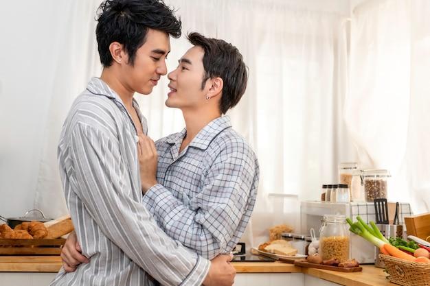 Pareja de homosexuales asiáticos abrazo y beso en la cocina en la mañana. concepto lgbt gay.