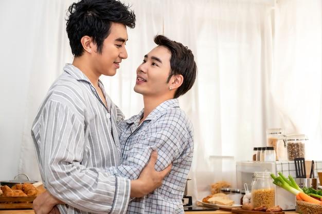 Pareja de homosexuales asiáticos abrazo y beso en la cocina en la mañana