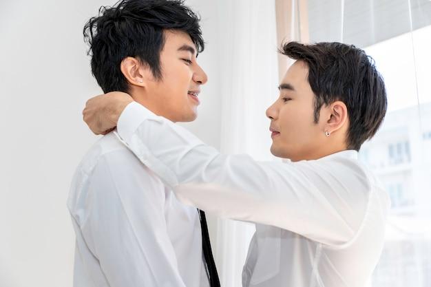 Pareja de homosexuales asiáticos ayudándose mutuamente a vestirse