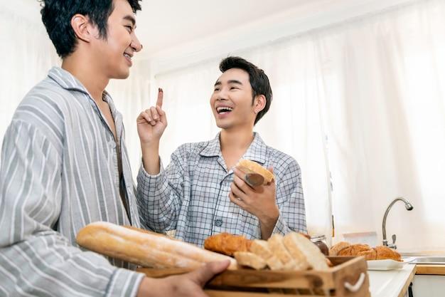 Pareja de homosexuales asiáticos cocinando el desayuno en la cocina en la mañana. concepto lgbt gay.
