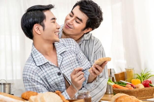 Pareja de homosexuales asiáticos cocinar el desayuno en la cocina en el morinking