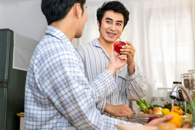 Pareja de homosexuales asiáticos feliz y divertida cocina ensalada en la cocina. concepto lgbt gay.
