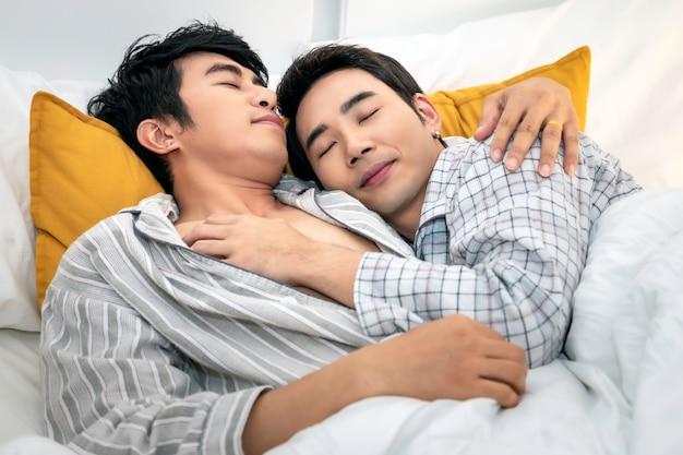 Pareja de homosexuales asiáticos en pijama dulce sueño y durmiendo en el dormitorio. concepto lgbt gay.