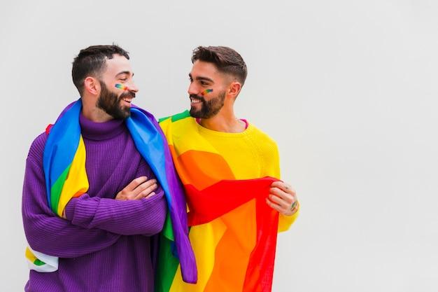 Pareja de homosexuales con banderas lgbt en los hombros sonriendo juntos