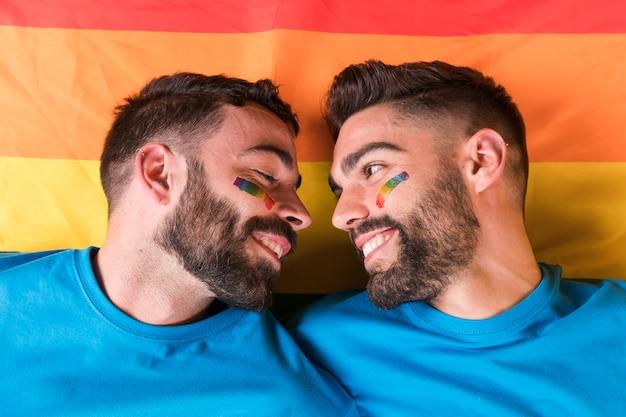 Pareja de homosexuales cara a cara apoyados el uno al otro en la bandera del arco iris