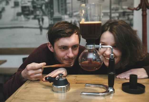 Pareja ilusionada observando una máquina de café