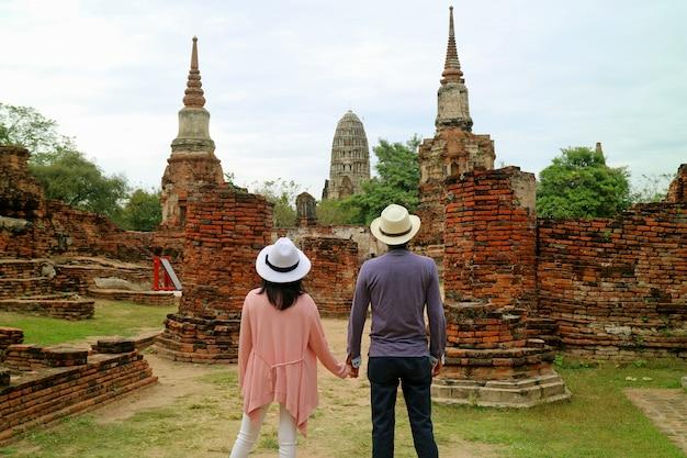 Pareja impresionada por las impresionantes ruinas del templo en el parque histórico de ayutthaya, tailandia