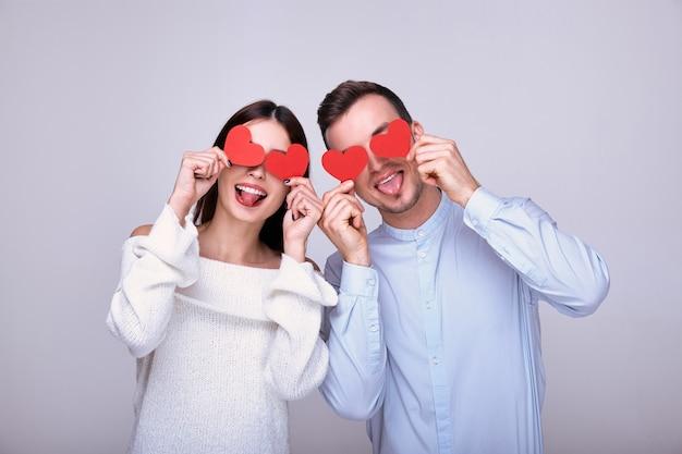 Una pareja increíblemente increíble de amantes con corazones de cartón rojo en las manos cerca de los ojos, fiesta de san valentín.