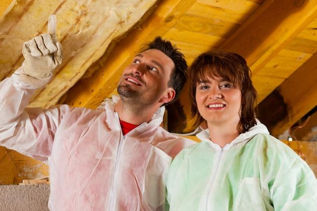 Pareja instalando aislamiento térmico en el techo